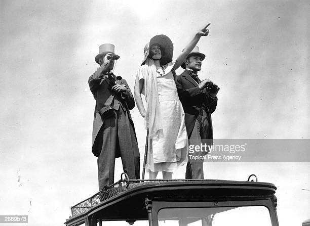 Spectators at the 1922 Epsom Derby stand on the roof of their car for a better view of the race.