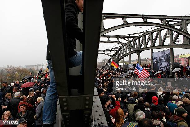 Spectators at the bridge at Bornholmer Strasse try to take a look at German Chancellor Angela Merkel former Soviet President Mikhail Gorbachev and...