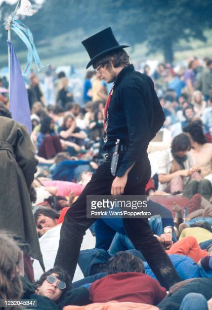 Spectators at the Isle of Wight Pop Festival, one attired in black, wearing a top hat and carrying a pocket knife at Newport on the Isle of Wight,...