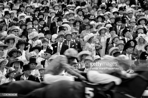 Spectators at the Royal Ascot horse race meeting watch the finish of a race, Berkshire, England, circa July 1976. This image is from a series of...