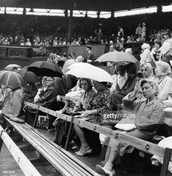 Spectators at Wimbledon's centre court waiting patiently under their umbrellas for the rain to stop