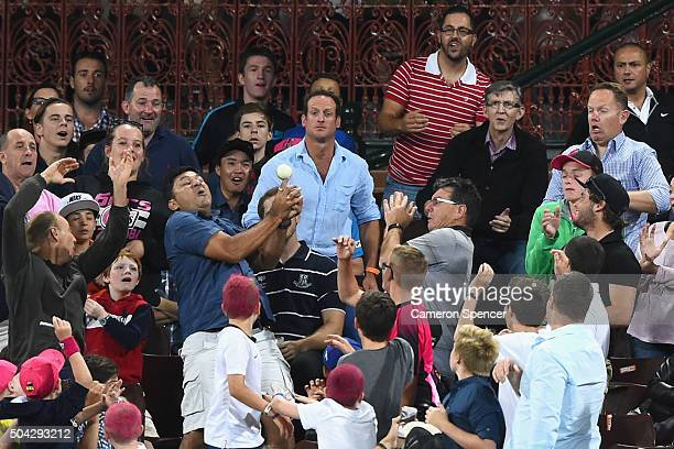 Spectators attempt to catch a ball hit for six runs during the Big Bash League match between the Sydney Sixers and the Brisbane Heat at Sydney...