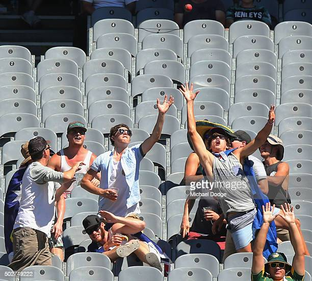 Spectators attempt to catch a six hit by Jason Holder of the West Indies off Nathan Lyon of Australia during day four of the Second Test match...