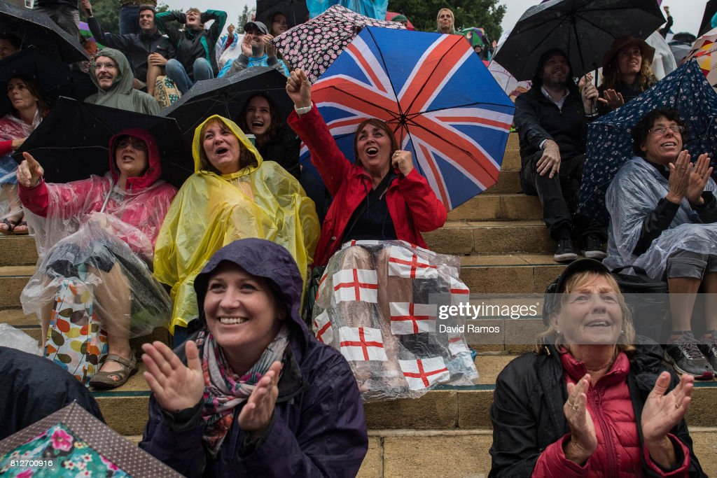 Spectators attempt to keep dry as they watch action on the screen on day eight of the Wimbledon Lawn Tennis Championships at the All England Lawn Tennis and Croquet Club on July 11, 2017 in London, England.