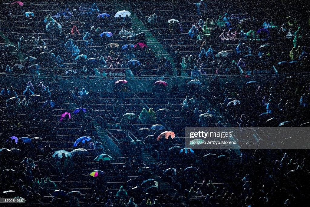 Spectators attend the La Liga match between FC Barcelona and Sevilla FC under a heavy reain at Camp Nou stadium grandstands on November 4, 2017 in Barcelona, Spain.