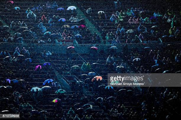 Spectators attend the La Liga match between FC Barcelona and Sevilla FC under a heavy reain at Camp Nou stadium grandstands on November 4 2017 in...