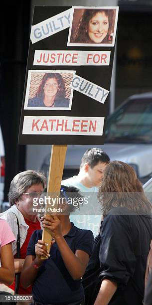 Spectators carry signs and chant while a news conference is held outside the Will County Courthouse after a jury found former Bollingbrook Illinois...