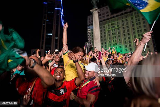 Spectators celebrate after watching Brazil defeat Germany to win the gold medal of the Men's Football final at the Olympic Boulevard live site during...