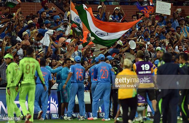 Spectators celebrate India's victory over Pakistan in the Pool B 2015 Cricket World Cup match between India and Pakistan at the Adelaide Oval on...