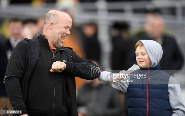 Spectators celebrate with a 'Elbow bump' during Silver Cups Day at Kempton Park on March 14 2020 in Sunbury England