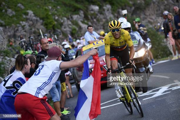 spectators cheer as Belgium's Greg Van Avermaet wearing the overall leader's yellow jersey rides up the Colombiere pass during the tenth stage of the...