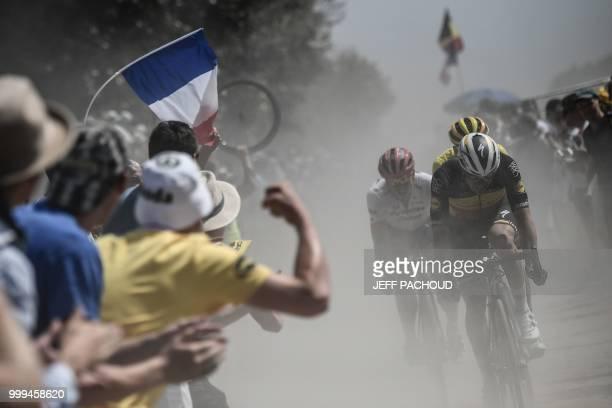 Spectators cheer as Belgium's Yves Lampaert , Belgium's Greg Van Avermaet , wearing the overall leader's yellow jersey, and Germany's John Degenkolb...