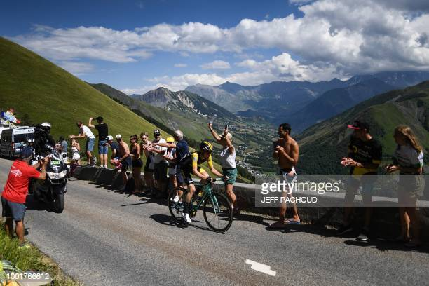 Spectators cheer as breakaway rider Netherlands' Steven Kruijswijk rides ahead of the stage up the Col de la Croix de Fer pass during the twelfth...