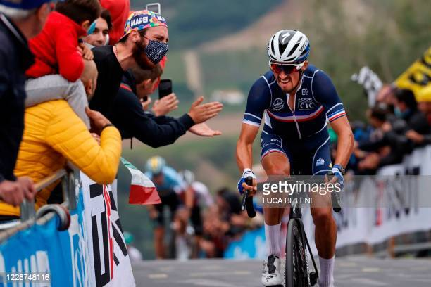 Spectators cheer as France's Julian Alaphilippe rides during his breakaway on his way to win the Men's Elite Road Race, a 258.2-kilometer route...