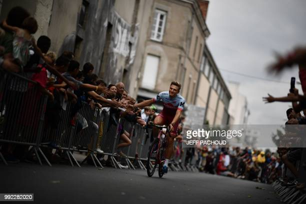 Spectators cheer as Germany's Marcel Kittel of Switzerland's Katusha Alpecin cycling team cycles past during the team presentation ceremony on July 5...