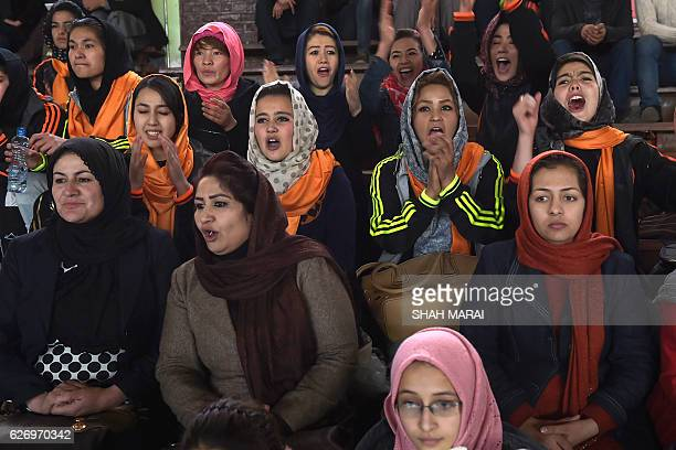 Spectators cheer as members of an Afghan women's volleyball team play in the final round of a volleyball tournament at the Kabul University in Kabul...