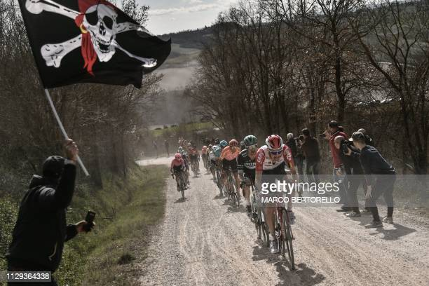 Spectators cheer as the pack rides through a gravel road during the one-day classic cycling race Strade Bianche on March 9, 2019 around Siena,...