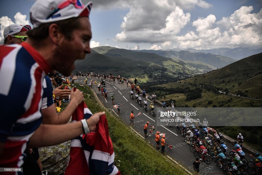 TOPSHOT - Spectators cheer as the pack rides uphill during the 17th stage of the 105th edition of the Tour de France cycling race, between Bagneres-de-Luchon and Saint-Lary-Soulan Col du Portet, southwestern France, on July 25, 2018.