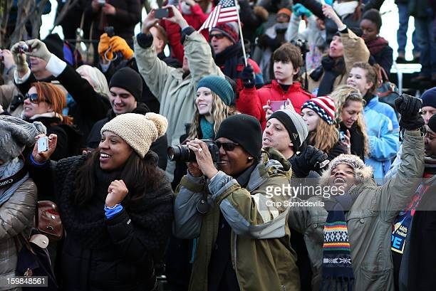Spectators cheer as the presidential inaugural parade winds through the nation's capital January 21 2013 in Washington DC Barack Obama was reelected...