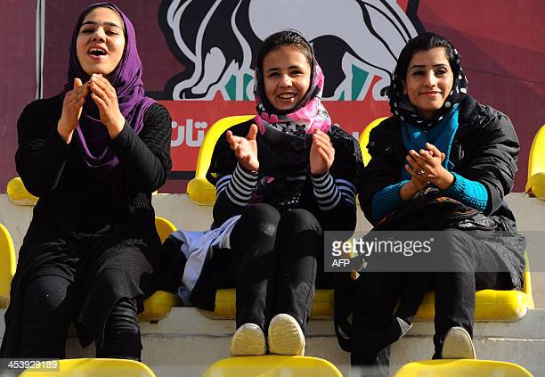Spectators cheer as they watch female football players from Isteghlal and Afghan compete during the women's football tournament final match in Kabul...