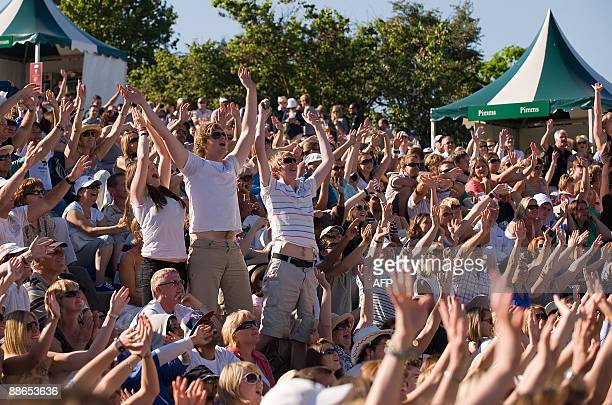 Spectators cheer as they watch tennis on a giant screen placed near Murray Mount at the 2009 Wimbledon tennis championships at the All England Club...