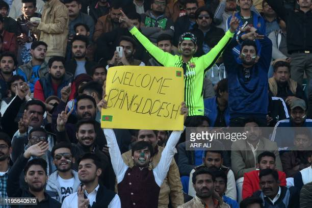Spectators cheer as they watch the first T20 international cricket match of a three-match series between Pakistan and Bangladesh at Gaddafi Cricket...