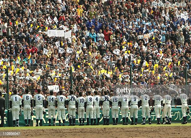 Spectators cheer baseball players of the Tohoku high school at the Koshien Stadium in Nishinomiya suburban Osaka on March 28 2011 The baseball team...