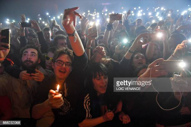 Spectators cheer during a concert at the 39th edition of the Trans Musicales music festival in SaintJacquesdelaLande outside Rennes northwestern...
