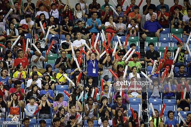 Spectators cheer during the World University Championship Floorball match between Malaysia and Singapore at the Sports Hub OCBC Arena on June 18 2014...