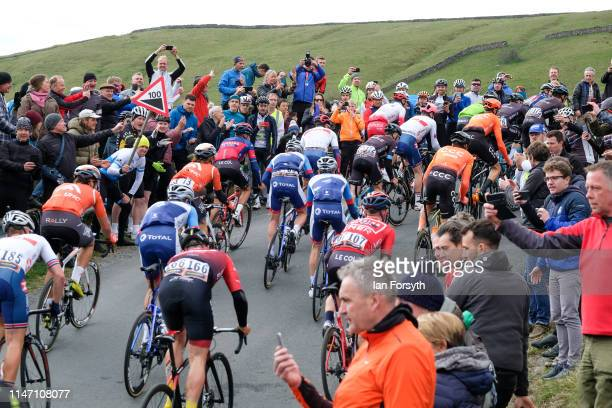 Spectators cheer for riders in the peloton on the Cote de Park Rash ascent near the village of Kettlewell in the Yorkshire Dales during the fourth...