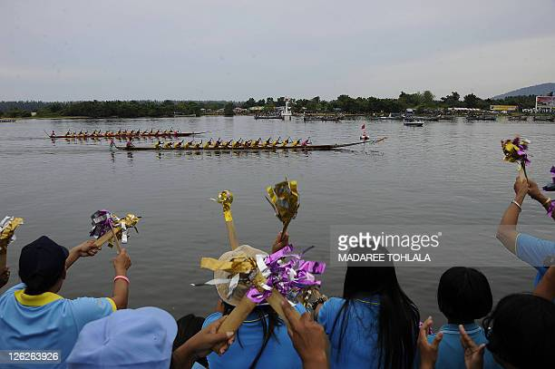 Spectators cheer for their teams during a dragon boat race on the Narathiwat river in Thailand's southern Narathiwat province on September 24 2011...