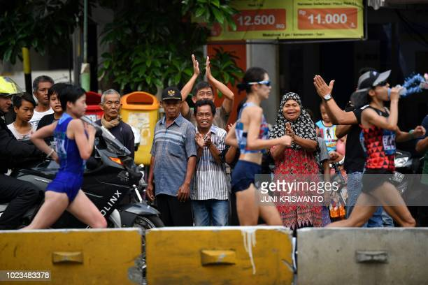 Spectators cheer on the athletes competing in the women's marathon athletics event during the 2018 Asian Games in Jakarta on August 26 2018