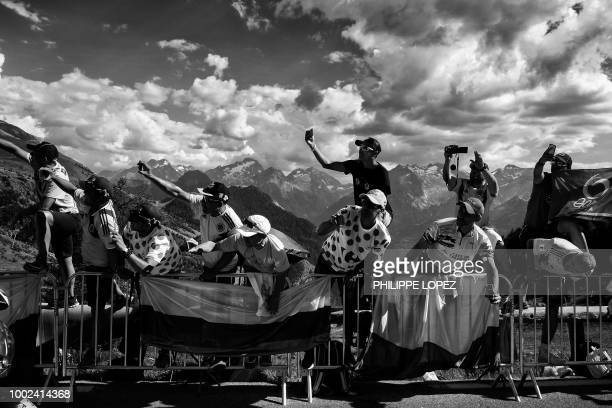 Spectators cheer riders during the twelfth stage of the 105th edition of the Tour de France cycling race between BourgSaintMaurice Les Arcs and...