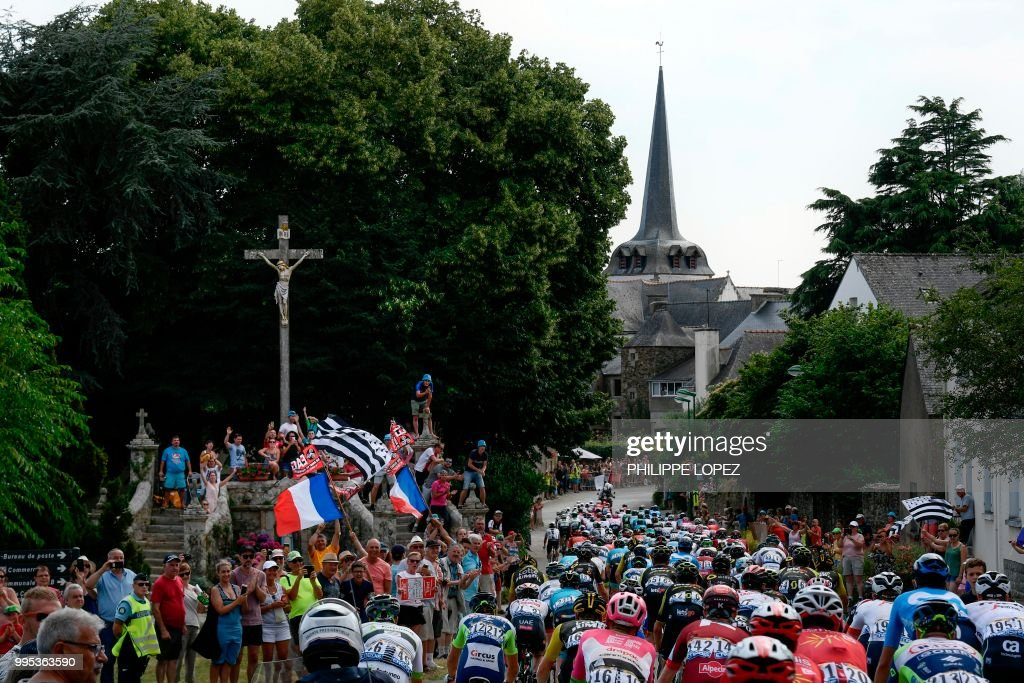 Spectators cheer the pack riding through the village of Noyal-Muzillac during the fourth stage of the 105th edition of the Tour de France cycling race between La Baule and Sarzeau, western France, on July 10, 2018.