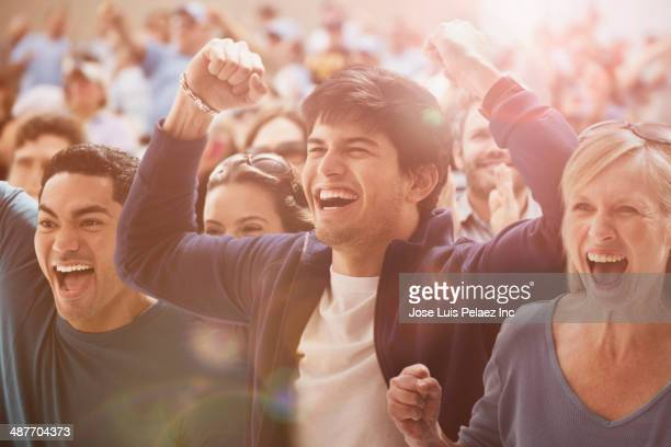 spectators cheering at sporting event - cheering ストックフォトと画像