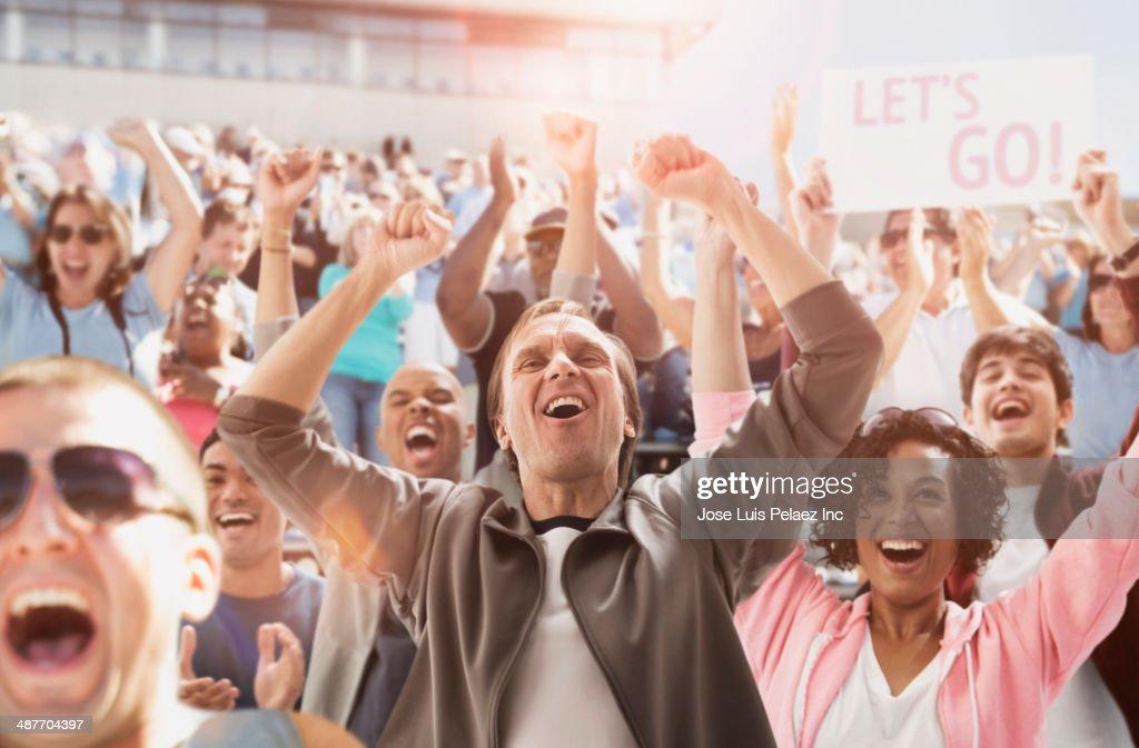 Spectators cheering at sporting event : Stockfoto