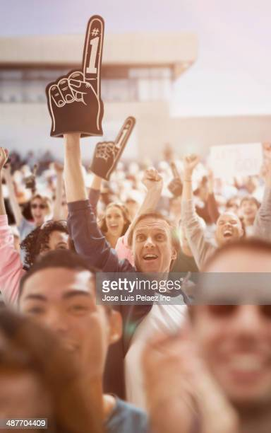 spectators cheering at sporting event - foam finger stock photos and pictures