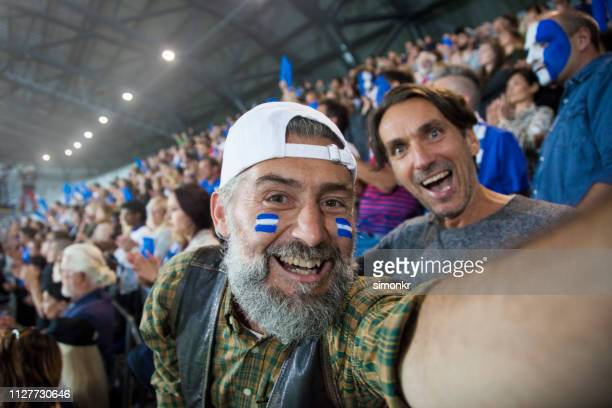 spectators cheering in stadium - match sport stock pictures, royalty-free photos & images