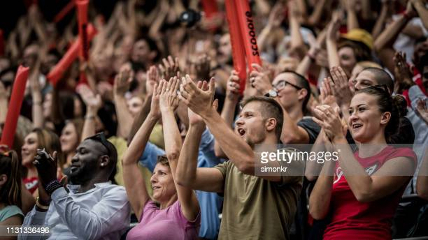 spectators cheering in stadium - cheering stock pictures, royalty-free photos & images