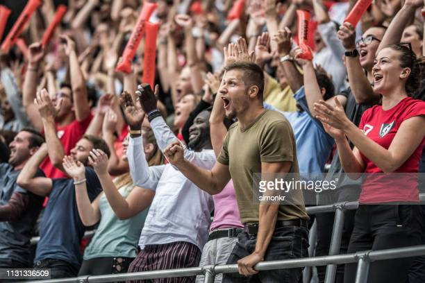 spectators cheering in stadium - sport stock pictures, royalty-free photos & images