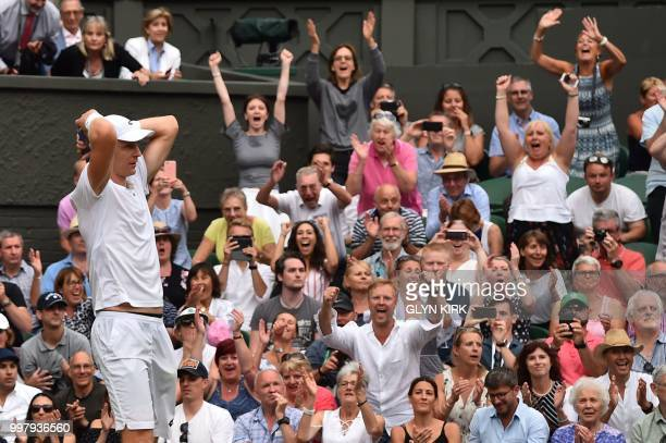 TOPSHOT Spectators cheers as South Africa's Kevin Anderson reacts after winning against US player John Isner during the final set tiebreak of their...