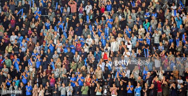 spectators clapping hands in stadium - spectator stock pictures, royalty-free photos & images