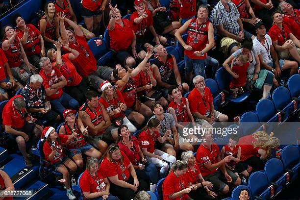 Spectators collect Christmas merchandise discount baubles during the round 10 NBL match between the Perth Wildcats and Melbourne United at Perth...