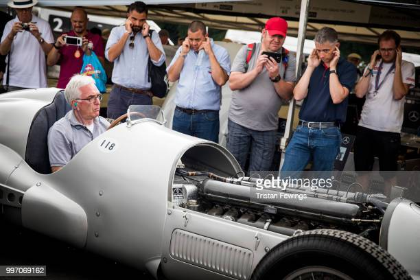 Spectators cover their ears as a mechanic starts up a classic MercedesBenz racing car during the Goodwood Festival Of Speed at Goodwood on July 12...