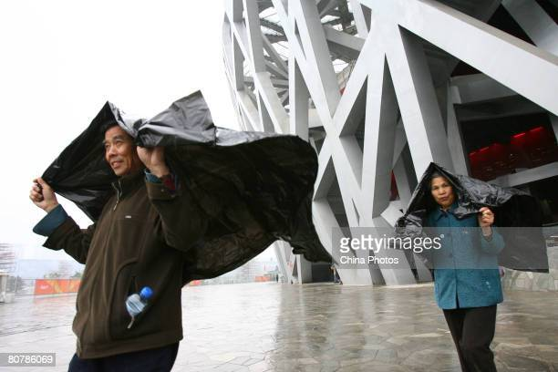 Spectators cover themselves with plastic as they leave the National Stadium to watch the 'Good Luck Beijing' 2008 Beijing International Marathon Race...