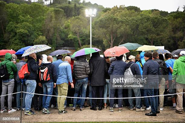 Spectators cover under umbrellas as rain falls on Day Four of The Internazionali BNL d'Italia on May 11 2016 in Rome Italy