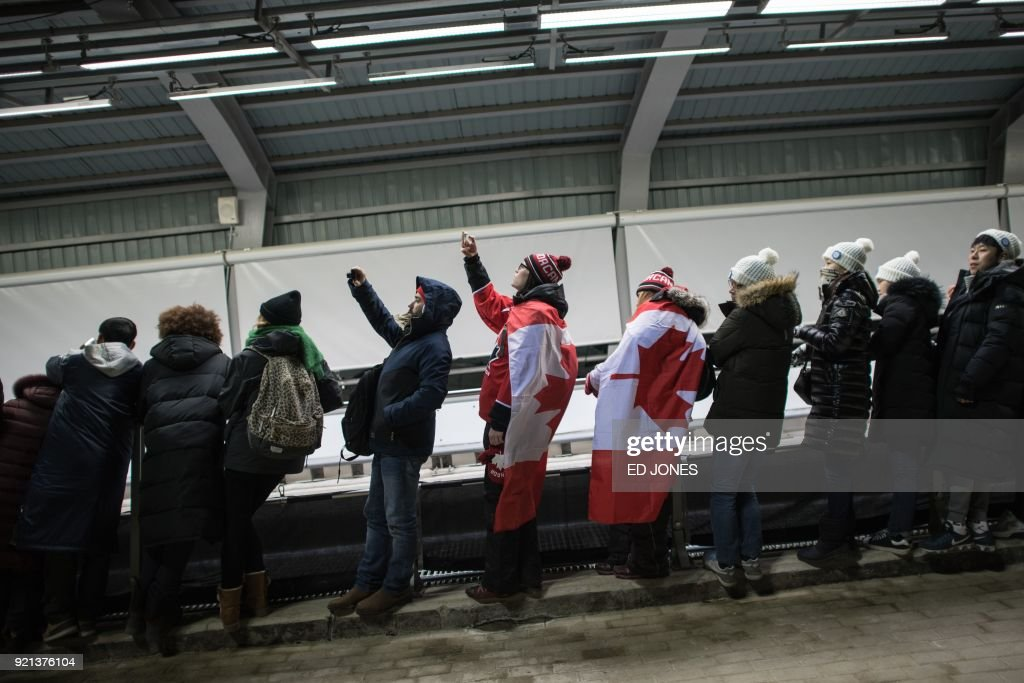 Spectators draped in Canada flags stand beside the track during the women's bobsleigh heats during the Pyeongchang 2018 Winter Olympic Games at the Olympic Sliding Centre in Pyeongchang on February 20, 2018. / AFP PHOTO / Ed JONES