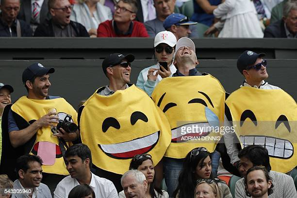 Spectators dressed as emoticons stand in the crowd watching Switzerland's Roger Federer play against Argentina's Guido Pella during their men's...