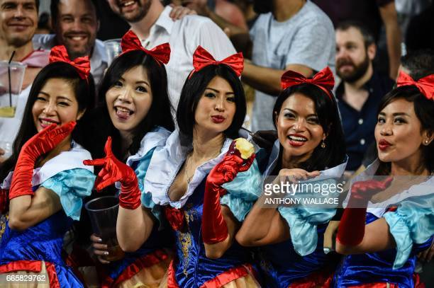Spectators dressed up as Disney character Snow White pose for a photo on the first day of the Rugby Sevens Tournament in Hong Kong on April 7 2017 /...