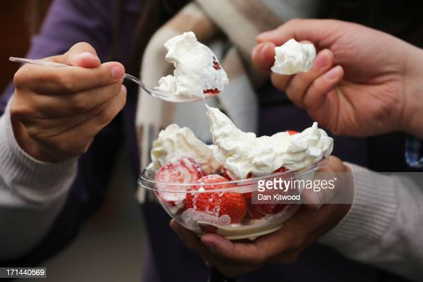 Spectators enjoy a bowl of strawberries and cream on day one of the Wimbledon Lawn Tennis Championships at the All England Lawn Tennis and Croquet...